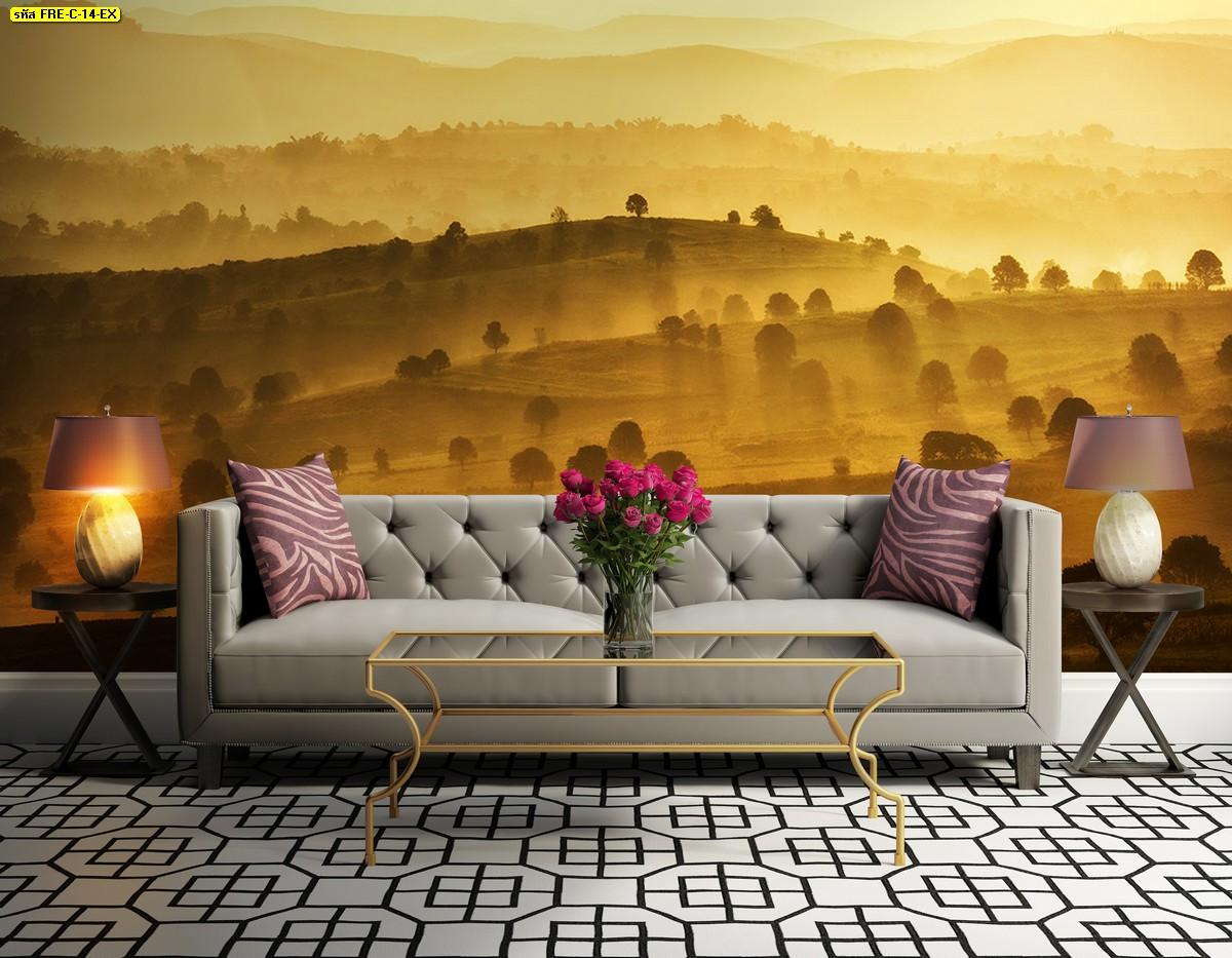 จัดแจกันดอกไม้ไว้กลางโต๊ะในห้องรับแขกสวยๆ ติดภาพวิวท้องฟ้าสีเหลืองทองสร้างบรรยากาศอบอุ่น